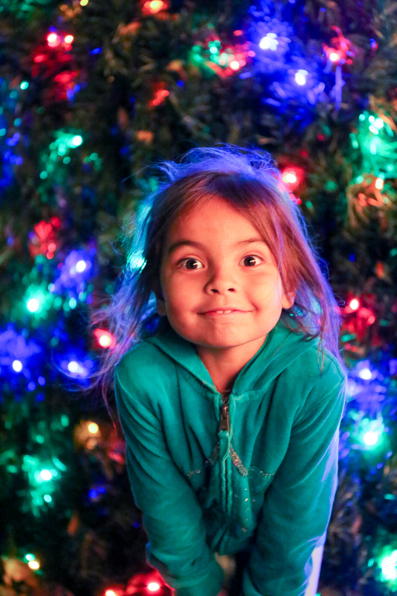 unclose of girl smiling with tree in the background